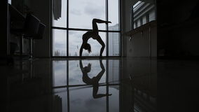 Incredible gymnastic exercises by the window. A young belerina in the studio and a mesmerizing reflection in the mirror stock video