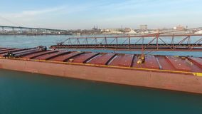 Incredible 4k aerial flight over large cargo freight container ship oil tanker vessel sailing in icy cold river water stock video