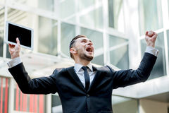 Incredible luck. Happy businessman celebrates his success. young. Man raises his hands. Businessman holding tablet in hand Royalty Free Stock Image