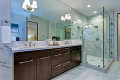 Incredible master bathroom with Carrara marble tile surround. Incredible master bathroom with Carrara marble tile surround, modern glass walk in shower royalty free stock photography