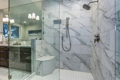 Incredible master bathroom with Carrara marble tile surround. Incredible master bathroom with Carrara marble tile surround, modern glass walk in shower and royalty free stock images