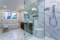 Incredible master bathroom with Carrara marble tile surround. Incredible master bathroom with Carrara marble tile surround, modern glass walk in shower royalty free stock image