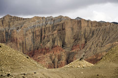 Incredible mineral landscape of Upper Mustang. Multicolored cliffs and piles of stones. Geological strata from gray to red. Pass, cairn and flag Stock Images
