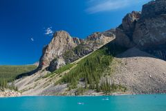 Incredible Moraine Lake. Canoes and tourists on beautiful Moraine Lake, Canada Royalty Free Stock Image