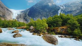 The incredible nature of Norway is a turbulent river from the melted waters of the Briksdal Glacier. Briksdal glacier with a mountain river in the foreground royalty free stock photo