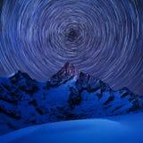 Incredible night view in Swiss Alps. Star trails moving in blue sky. Zermatt resort location, Weisshorn, Switzerland. royalty free stock image