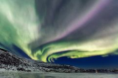 Northern lights. Incredible Northern lights Aurora Borealis activity above the coast in Norway Royalty Free Stock Photo