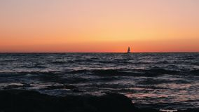 Incredible orange sunset with small sailboat on horizon. Silhouette of small sailboat floating in sea at sunset. Silhouette of sai. Lboat in sea. Silhouette of stock video