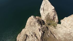 Incredible top 4k aerial drone view on huge stone rock mountain cliff in Lake Baikal calm water Russia Siberia seascape stock footage