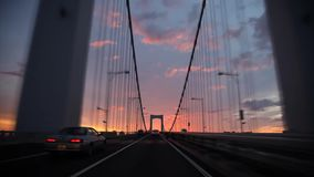 Bridge busy traffic highway road from wind shield glass first person pov with incredible warm orange evening sunset sky. Incredible warm evening sunset sky over stock footage