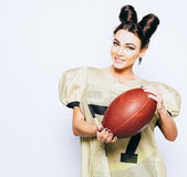 Incredibly beautiful, athletic brunette girl in American football uniform showing the ball inviting to the game royalty free stock photos