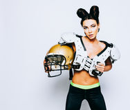 An incredibly beautiful, athletic brunette girl in a shoulderpads and an American football helmet demonstrating stunning. Amazing abs. White background. Footy Stock Photo