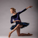 Incredibly beautiful ballerina with perfect body in blue outfit posing in studio. classical ballet art. stock photo