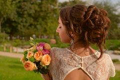 Incredibly beautiful bride with bouquet of roses. Romantic accessory of fiancee. Long haired girl in wedding gown.  Royalty Free Stock Images