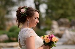 Incredibly beautiful bride with bouquet of roses. Romantic accessory of fiancee. Long haired girl in wedding gown.  stock photo
