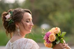 Incredibly beautiful bride with bouquet of roses. Romantic accessory of fiancee. Long haired girl in wedding gown.  Stock Images