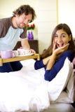 Incredibly lycklig ung gullig kvinna som får frukosten i säng royaltyfria bilder