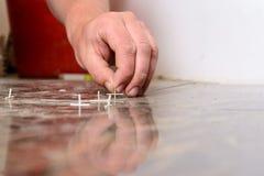 Incroci di plastica per la stenditura delle mattonelle sul pavimento immagine stock libera da diritti