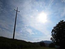 Incrocio ad alta tensione della siluetta della colonna di elettricità con fondo di cielo blu, del Sun e delle nuvole bianche Fotografia Stock Libera da Diritti