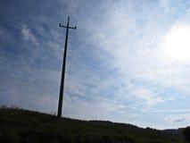 Incrocio ad alta tensione della siluetta della colonna di elettricità con fondo di cielo blu, del Sun e delle nuvole bianche Immagini Stock