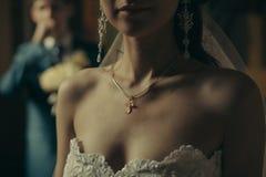 Incrocio cristiano sulla sposa del petto Immagine Stock