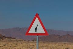 Incrocio della giraffa di Roadsign in Africa Immagini Stock