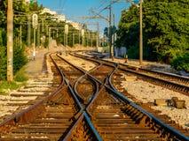 Incrocio di ferrovia con gli alberi ed il cielo blu verdi fotografia stock libera da diritti
