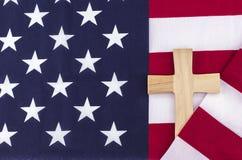 Incrocio di legno avvolto in bandiera americana Immagini Stock