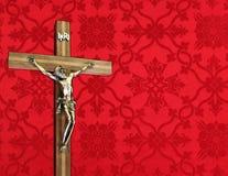Incrocio di legno con il corpo del metallo di Cristo sul modello rosso fotografie stock libere da diritti
