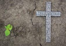 Incrocio di legno con la preghiera del ` s di signore sulla terra con un fondo della pianta verde Fotografie Stock