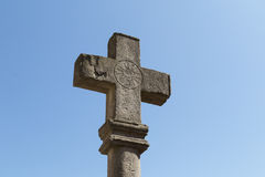 Incrocio di pietra antico con la marcatura ed il cielo blu solari Fotografie Stock