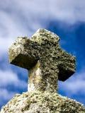 Incrocio di pietra con le piante con il cielo come fondo immagini stock