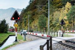 Incrocio di Railraod con le luci d'avvertimento di lampeggiamento e un treno rosso che si avvicina nella campagna svizzera immagine stock