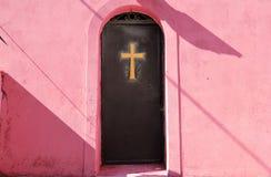 Incrocio dorato su una porta del metallo Fotografie Stock Libere da Diritti