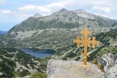 Incrocio dorato sul picco di montagna fotografia stock