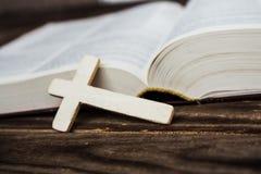 Incrocio e bivle cristiani su fondo di legno Fotografia Stock