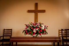 Incrocio e fiori cristiani sull'altare Fotografie Stock