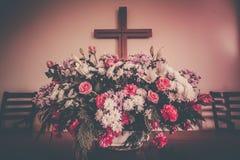 Incrocio e fiori cristiani sull'altare Immagine Stock Libera da Diritti