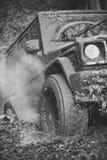 Incrocio nero che guida con la nuvola di fumo attraverso la sporcizia Immagini Stock