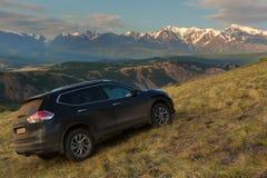 Incrocio Nissan X-Trail sul pendio di collina in steppa di Kurai contro il contesto della cresta del nord di Chuy all'alba Immagine Stock