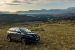 Incrocio Nissan X-Trail sul pendio di collina in steppa di Kurai contro il contesto della cresta del nord di Chuy all'alba Immagini Stock