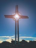 Incrocio Shinning sull'alta montagna rocciosa Croce artistica d'acciaio sopra la montagna alpina, Immagine Stock