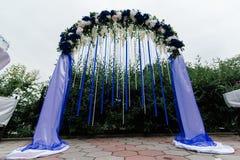 Incurvi con i fiori blu e bianchi, la pianta ed i nastri blu Fotografie Stock