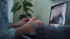 Indépendant à l'aide de l'ordinateur portable mangeant la banane à la maison Jeune homme établissant outre du bureau banque de vidéos