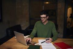 Indépendant émotif dans la veste verte utilisant la connexion sans fil à l'Internet dans le bureau Image stock