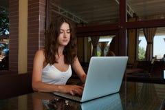indépendant assez féminin employant le filet-livre pour le travail de distance, fille d'étudiant apprenant par l'intermédiaire du photos libres de droits