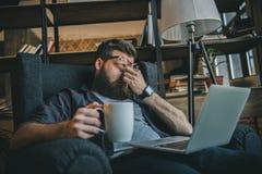 Indépendant barbu dans des lunettes utilisant l'ordinateur portable et le café potable à la maison photos stock
