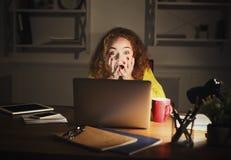 Indépendant choqué travaillant sur l'ordinateur portable à la maison jusqu'à fin de soirée Images stock