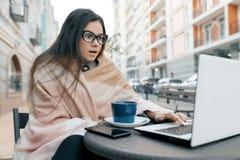 Indépendant de blogger de jeune femme dans des vêtements chauds en café extérieur avec l'ordinateur portable d'ordinateur, téléph image stock