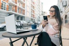 Indépendant de blogger de jeune femme dans des vêtements chauds en café extérieur avec l'ordinateur portable d'ordinateur, téléph photos libres de droits
